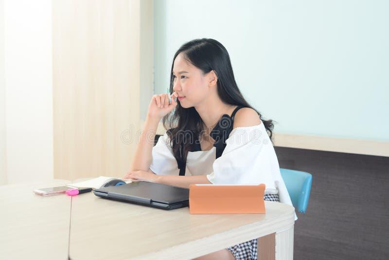 Ung asiatisk kvinnaworling och problem på skrivbordet i regeringsställning royaltyfri bild