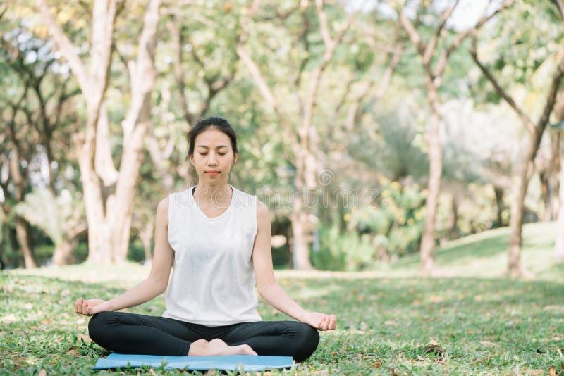 Ung asiatisk kvinnayoga håller stillhet och mediterar utomhus, medan öva yoga arkivfoto