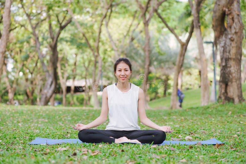 Ung asiatisk kvinnayoga håller stillhet och mediterar utomhus, medan öva yoga royaltyfria bilder