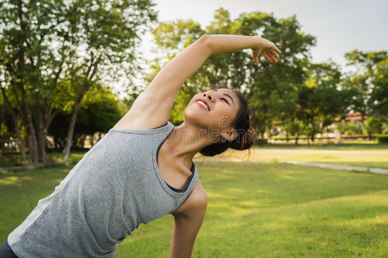 Ung asiatisk kvinnayoga håller stillhet och mediterar utomhus, medan öva yoga royaltyfria foton