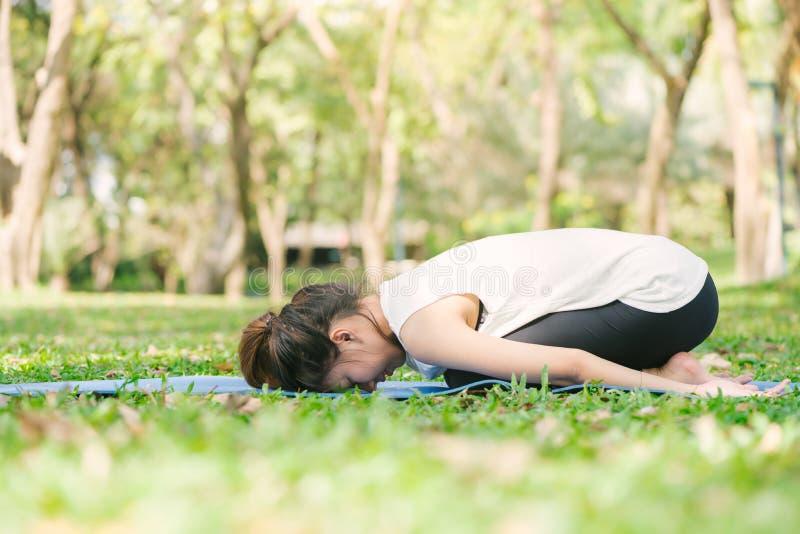 Ung asiatisk kvinnayoga håller stillhet och mediterar utomhus, medan öva yoga arkivfoton