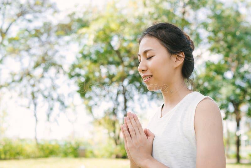 Ung asiatisk kvinnayoga håller stillhet och mediterar utomhus medan praktiserande yoga för att undersöka den inre freden arkivfoton