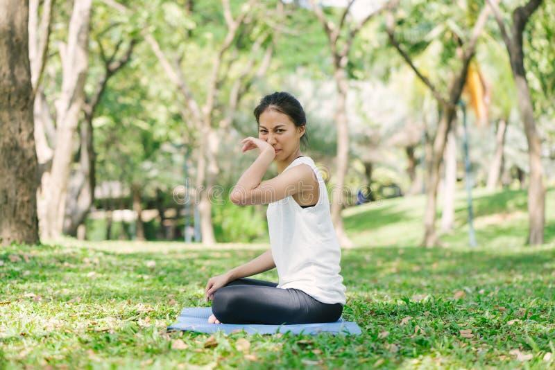 Ung asiatisk kvinnayoga håller stillhet och mediterar utomhus medan praktiserande yoga för att undersöka den inre freden fotografering för bildbyråer