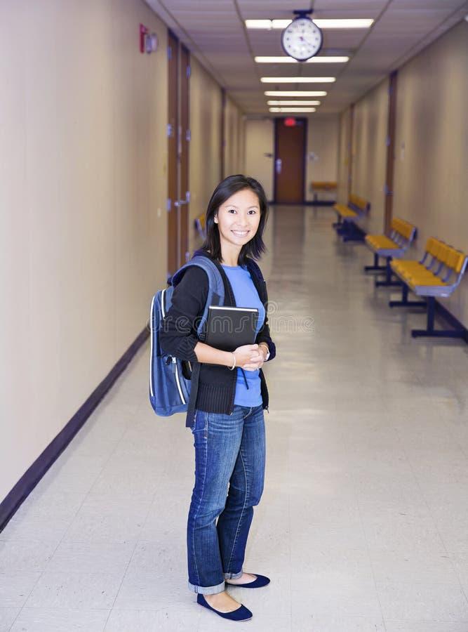 Ung asiatisk kvinnlig högskolaflicka i avläggande av examenkappan som isoleras på vit bakgrund fotografering för bildbyråer