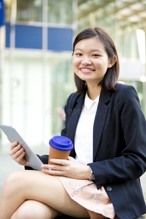 Ung asiatisk kvinnlig ledare som dricker kaffe och använder minnestavlaPC arkivfoto