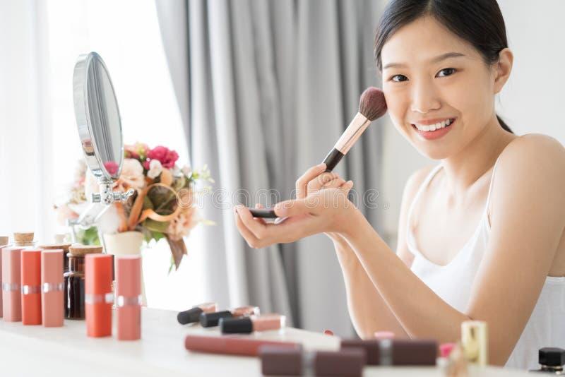 Ung asiatisk kvinnlig makeupskönhet vid borsten fotografering för bildbyråer