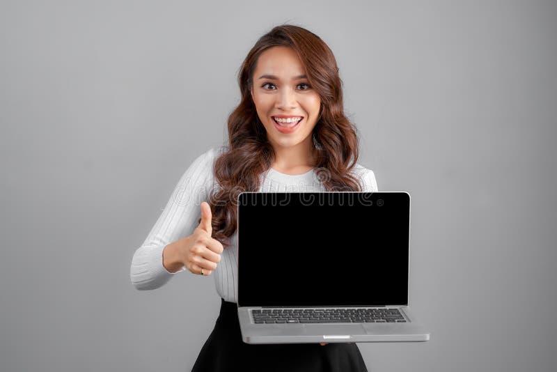 Ung asiatisk lycklig kvinna med anteckningsbokbärbara datorn som isoleras på grå bakgrund arkivbild