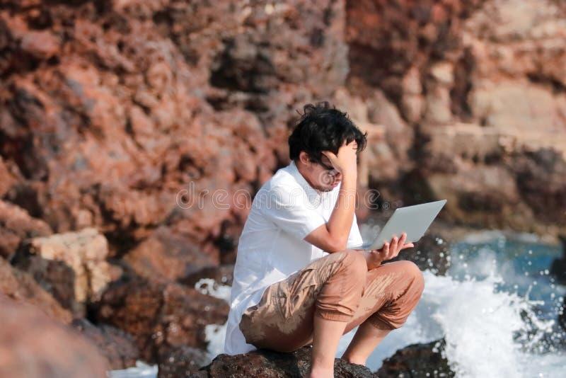 Ung asiatisk man för frustrerad ångest med bärbar datorlidande från strängt problem på havskusten arkivbilder