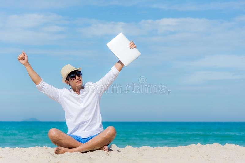 Ung asiatisk man för livsstil som kopplar av, når att ha arbetat på bärbara datorn, medan sitta på den härliga stranden, frilans- royaltyfri fotografi