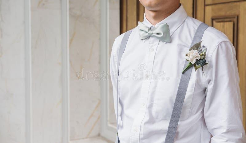 Ung asiatisk man för närbild i den vita skjortan med flugan och suspenderen royaltyfri fotografi