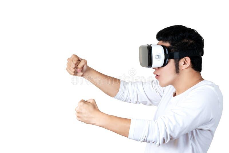 Ung asiatisk man i den tillfälliga dräkten som rymmer eller bär VR-exponeringsglasskyddsglasögon som spelar videospelet för sprin royaltyfria foton