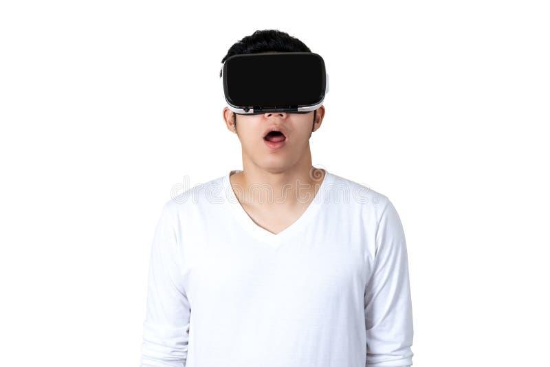 Ung asiatisk man i den tillfälliga vita dräkten som rymmer eller bär VR-exponeringsglas som håller ögonen på videoen arkivfoto