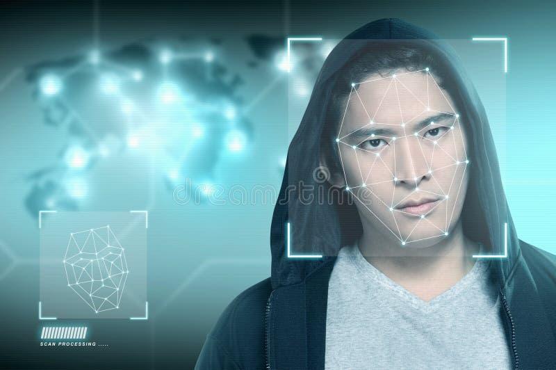 Ung asiatisk man i svart hoodie genom att använda framsidaerkännande royaltyfria foton