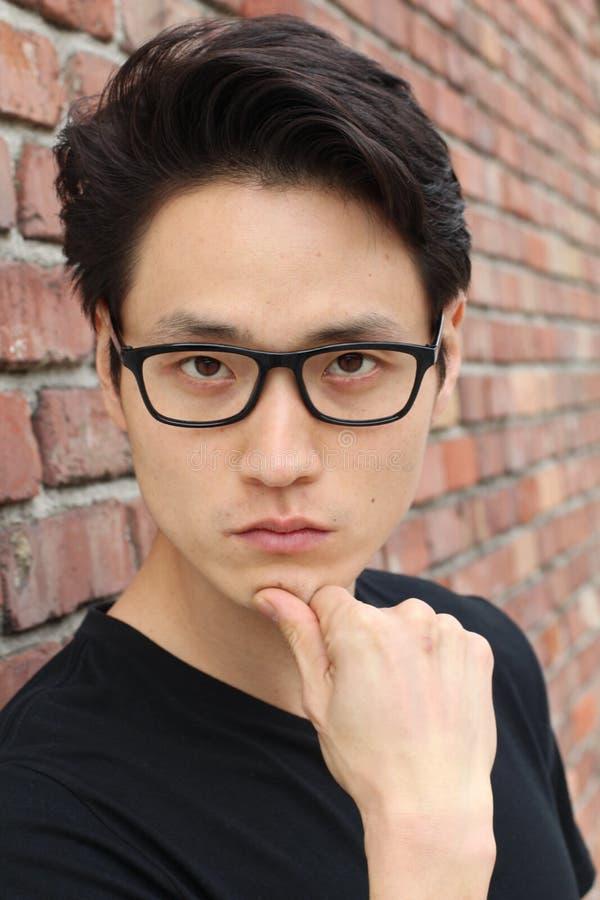 Ung asiatisk man med att tänka för exponeringsglas royaltyfri fotografi