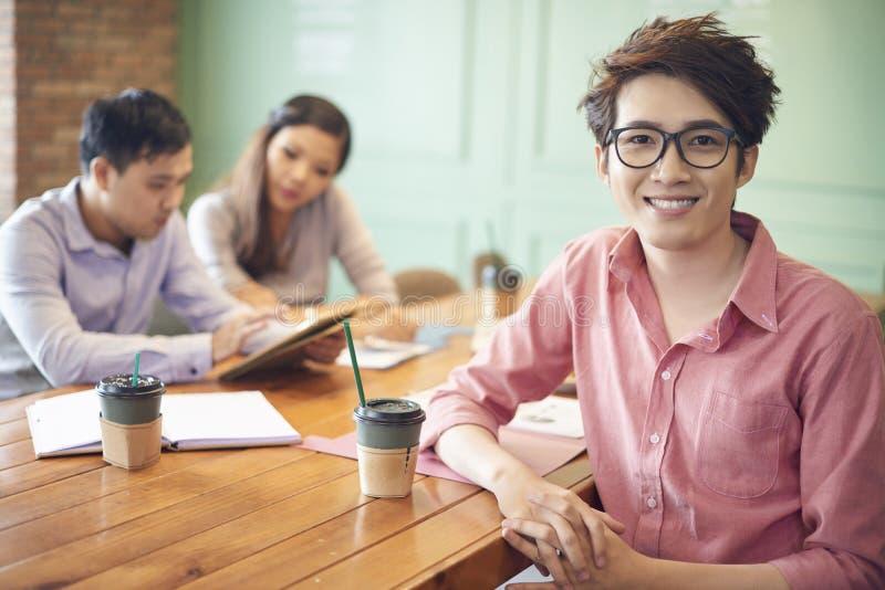 Ung asiatisk man med coworkers på kaffeavbrott fotografering för bildbyråer