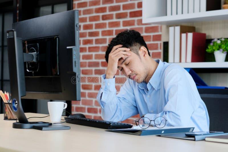 Ung asiatisk man med frustrerat uttryck, medan arbeta med datoren på kontorsskrivbordet, kontorslivsstil royaltyfria foton