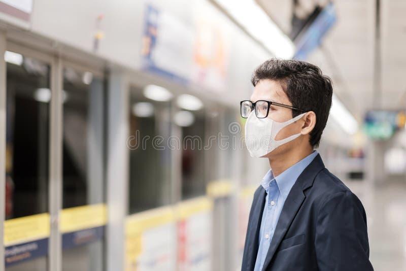 Ung asiatisk man med skyddsmask mot Novel coronavirus eller Corona Virus Disease Covid 19 på den offentliga tågstationen är en arkivbilder