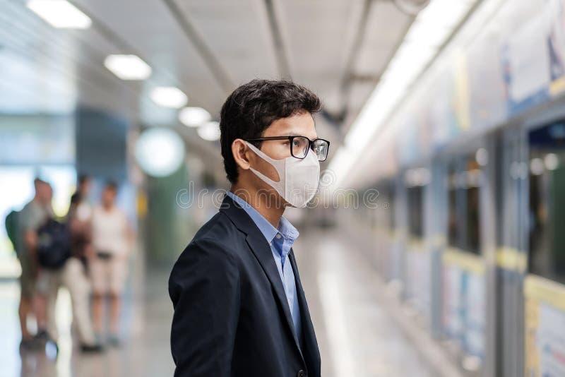 Ung asiatisk man med skyddsmask mot Novel coronavirus eller Corona Virus Disease Covid 19 på den offentliga tågstationen är en arkivbild