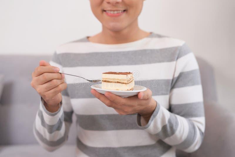 Ung asiatisk man som äter kakan, medan sitta på soffan hemma royaltyfria bilder