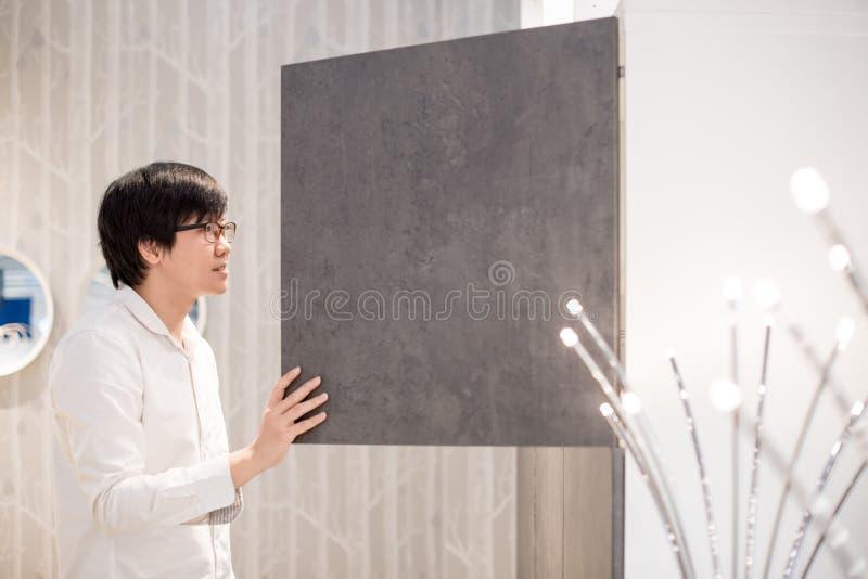 Ung asiatisk man som öppnar den moderna garderoben som väljer möblemang i wa fotografering för bildbyråer