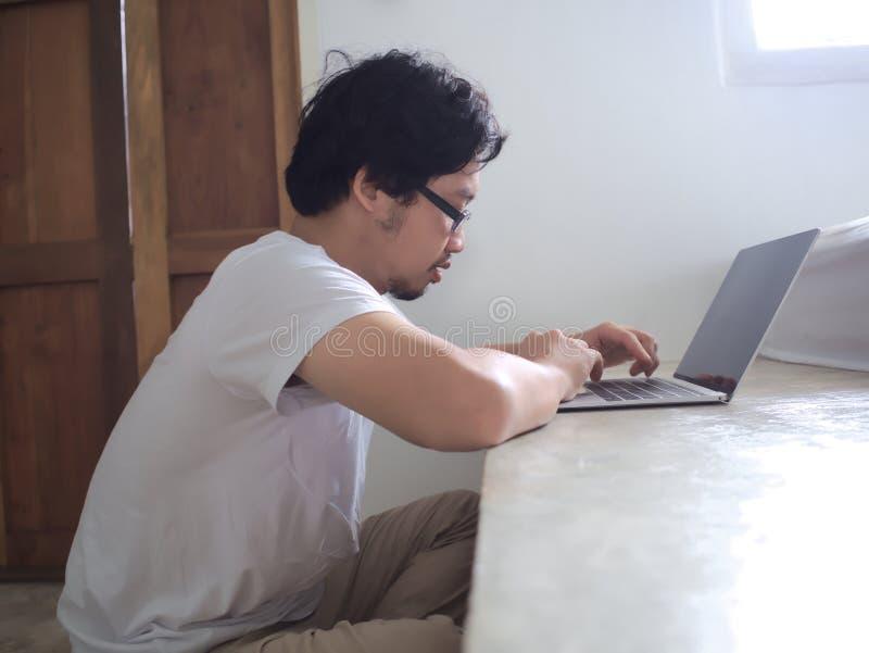 Ung asiatisk man som använder datorbärbara datorn i vardagsrum E arkivfoto