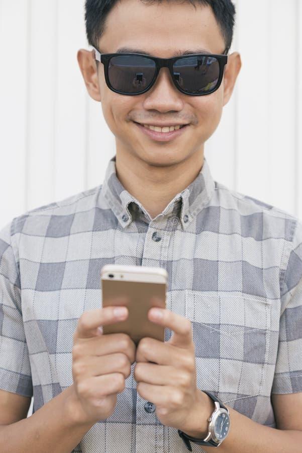 Ung asiatisk man som använder smartphonen royaltyfri foto