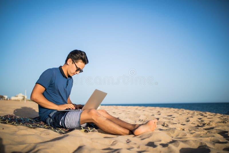 Ung asiatisk man som arbetar med bärbar datordatoren på den tropiska stranden Turist royaltyfri foto