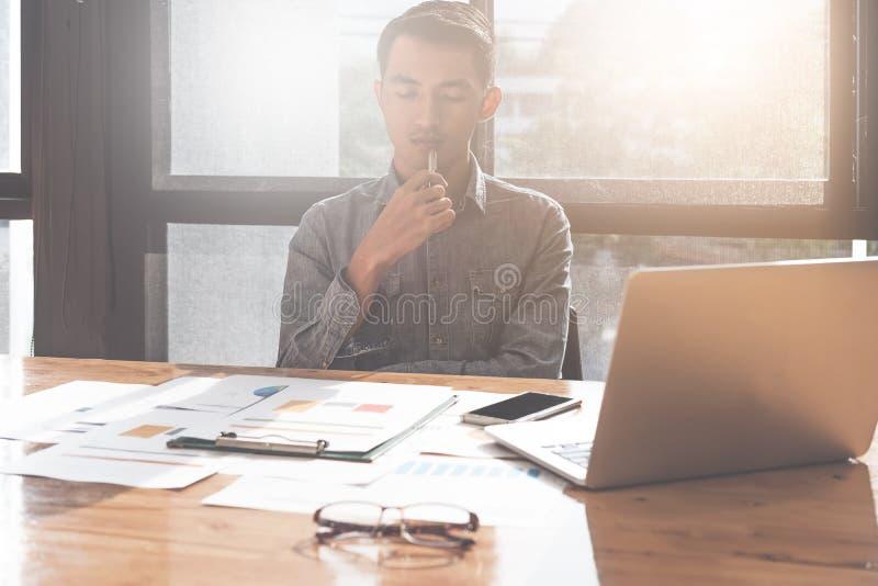 Ung asiatisk man som arbetar med det bärbar datordatoren och dokumentet medan royaltyfri fotografi