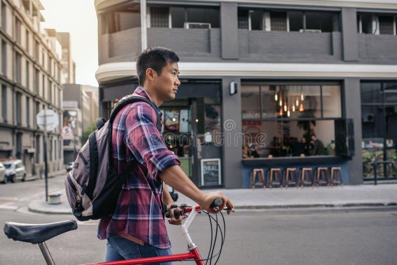 Ung asiatisk man som går med hans cykel i staden royaltyfri bild