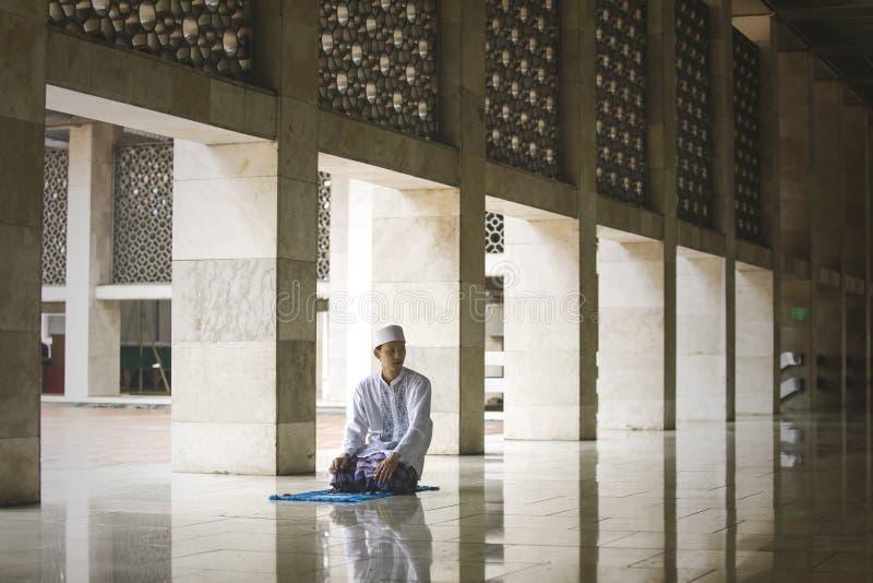 Ung asiatisk man som gör Salat på moskén arkivbild