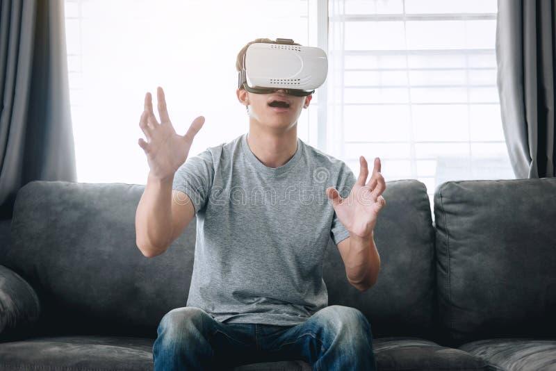 Ung asiatisk man som har gyckel som bär spela virtuell verklighethörlurar med mikrofonexponeringsglas till att tycka om i ferie arkivbild