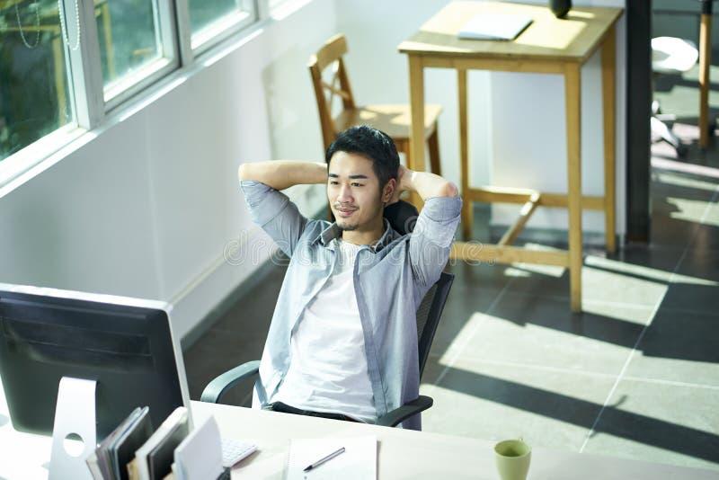 Ung asiatisk man som i regeringsställning ser datoren royaltyfri bild