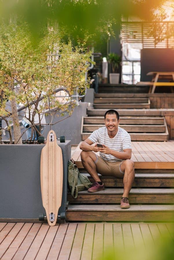 Ung asiatisk man som kopplar av på moment utanför läs- textmeddelanden royaltyfri foto