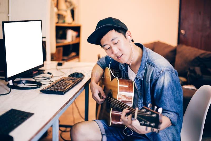 Ung asiatisk man som lär hur man spelar gitarren på datorbildskärm arkivbilder