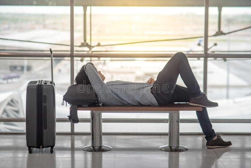 Ung asiatisk man som ligger på bänk i flygplatsterminal fotografering för bildbyråer