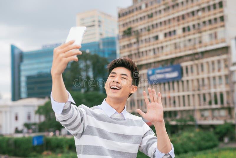 Ung asiatisk man som tar selfie på bakgrunden av staden royaltyfria foton