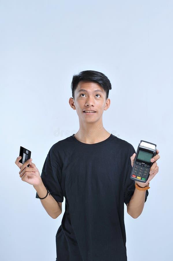 Ung asiatisk man som visar en kreditkort/ett debiteringkort och ett tillfångatagande för elektroniska data & en x28; EDC& x29; ma royaltyfria bilder