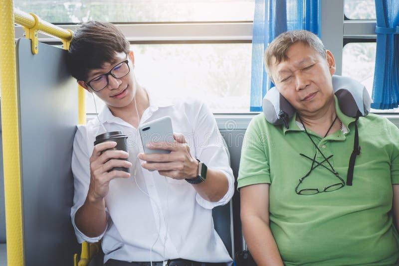 Ung asiatisk manhandelsresande som sitter på en buss genom att använda smartphonen för l arkivbild