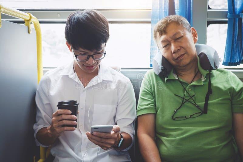Ung asiatisk manhandelsresande som sitter på en buss genom att använda smartphonen för lyssnande musik och mogna män som sover me royaltyfri fotografi