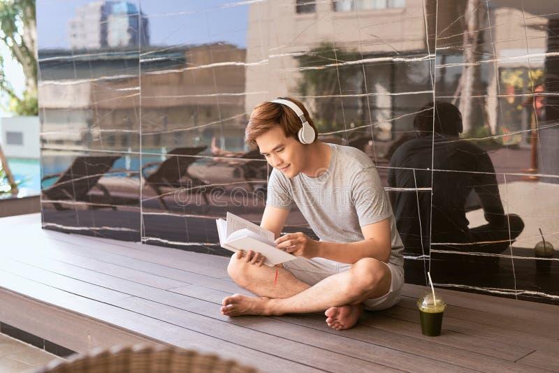 Ung asiatisk manläsebok och lyssna till musik vid pölen fotografering för bildbyråer