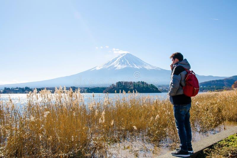 Ung asiatisk manställning som ser Mount Fuji på Kawaguchiko sjön på morgonen royaltyfri bild
