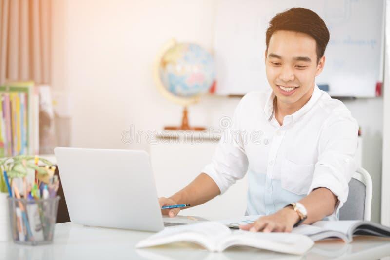 Ung asiatisk manuniversitetsstudent som arbetar med bärbar datordatoren fotografering för bildbyråer
