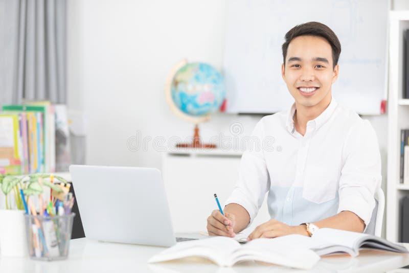 Ung asiatisk manuniversitetsstudent som arbetar med bärbar datordatoren arkivfoton