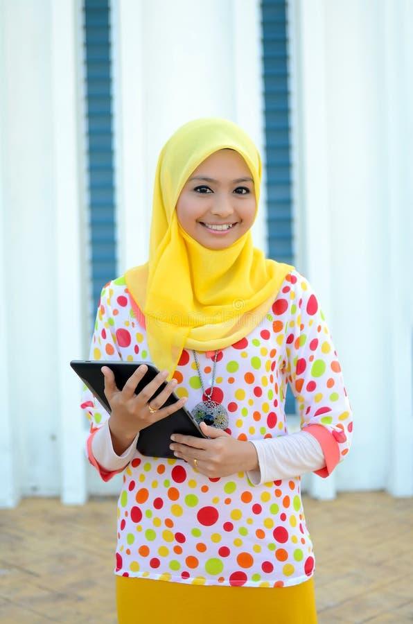 Ung asiatisk muslimkvinna i den head halsduken med den mobila bärbara datorn arkivfoto