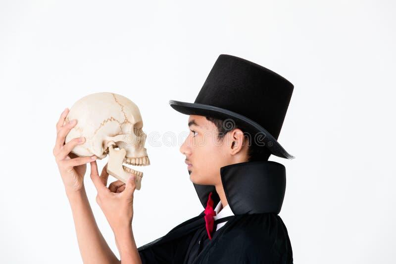 Ung asiatisk pojke i svart räkning och svarta hatten som rymmer och ser arkivbild