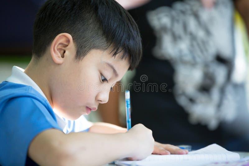 Ung asiatisk pojke som gör hans läxa royaltyfri fotografi