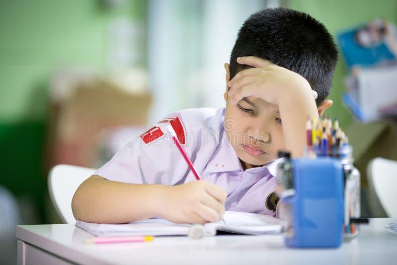 Ung asiatisk pojke som gör hans läxa arkivfoto