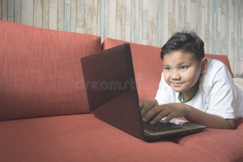 Ung asiatisk pojke som hemma använder bärbar datordatoren på en soffa arkivfoton