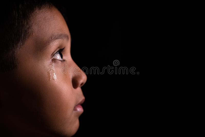 Ung asiatisk pojke som ser in i ljus i mörker med revor i hans öga royaltyfri bild