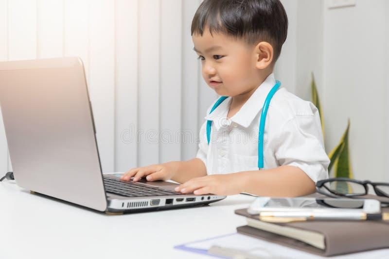 Ung asiatisk pojke som spelar doktorn och använder datorbärbara datorn royaltyfria foton